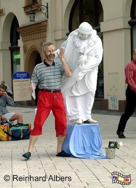Dieser Straßenkünstler bezieht bei seinen Auftritten auch das Publikum mit ein., Polen, Polska, Kraków, Krakau, Bilder, Fotos, Straßenkünstler, Pantomime,